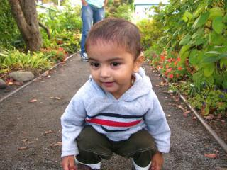 Child crouching down on a path outside